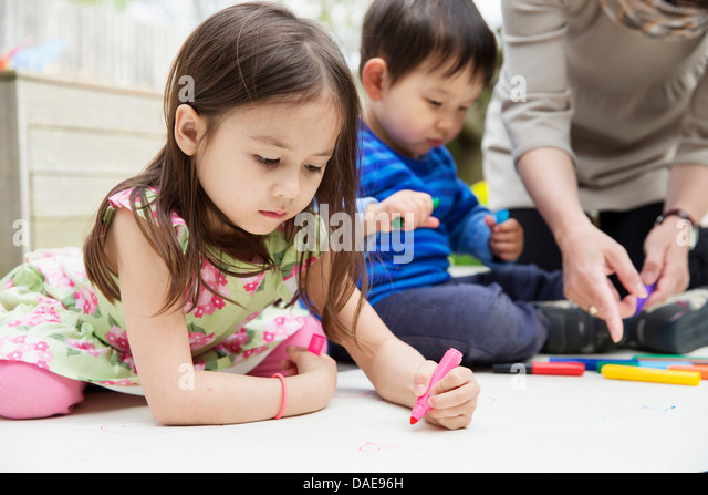 Mother and two children drawing in garden - Stock Image