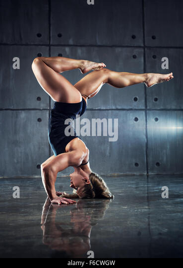 Strong woman bodybuilder standing upside down on wall background. - Stock Image