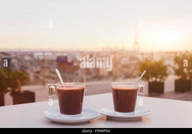 two cups of coffee or hot chocolate and Paris skyline at sunset, cafe with panoramic view of the city with Eiffel - Stock-Bilder