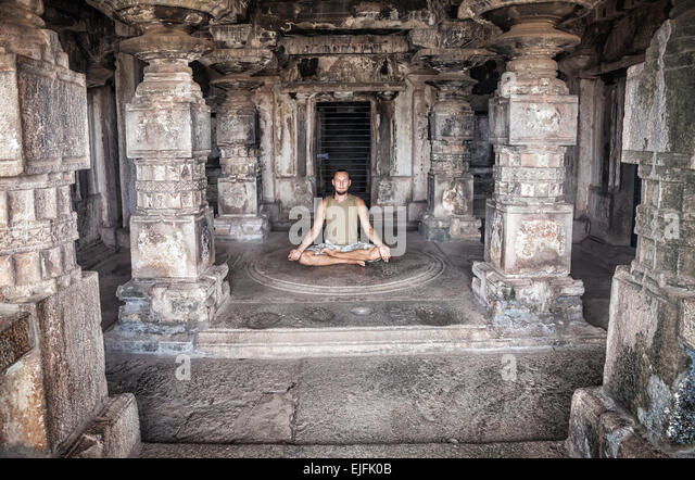 Man doing meditation in ancient temple with carving columns in Hampi, Karnataka, India - Stock Image