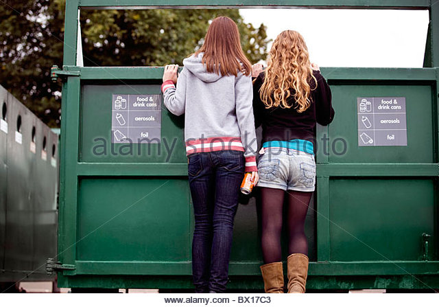 Two teenage girls looking into a recycling container - Stock Image