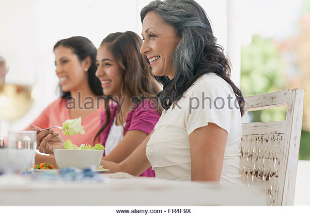 profile of mother and daughters at dinner table - Stock-Bilder