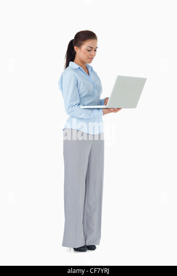 Professional woman working on laptop against a white background - Stock Image