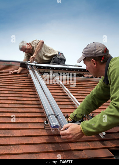 self building house, men fitting Veissmann Solar Thermal Hot Water tubes to south facing roof - Stock Image