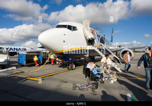 Passengers disembarking a Ryanair Flight at Stansted Airport whilst luggage is being unloaded including baby buggies - Stock Image