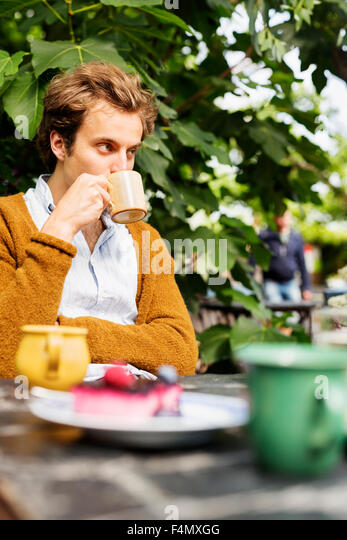 Man drinking coffee with cake served on table at greenhouse - Stock-Bilder