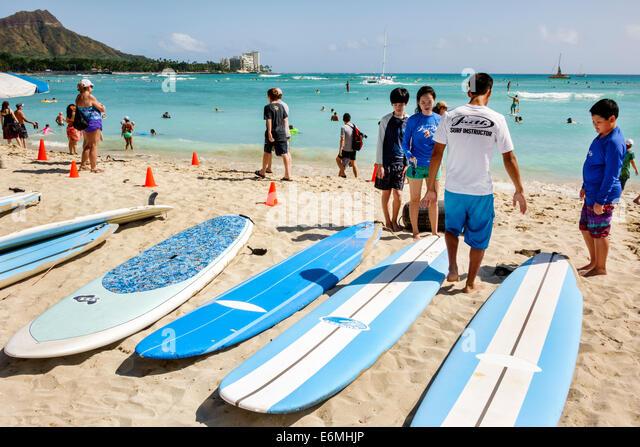 Waikiki Beach Honolulu Hawaii Hawaiian Oahu Pacific Ocean waterfront sunbathers surfboard surfer surfboard surfing - Stock Image