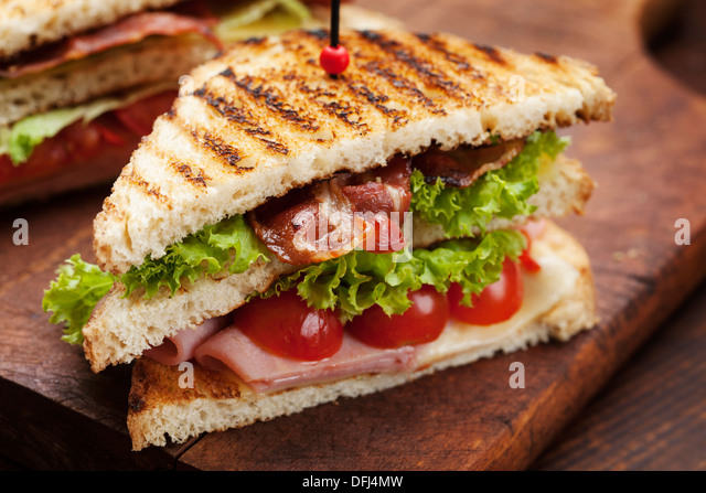 close up of fresh sandwich with ham, bacon,tomatoes,cheese and lettuce - Stock Image
