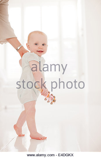 Parent helping baby walk - Stock Image