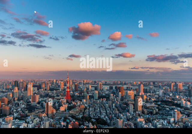 Tokyo Tower stands out among the Tokyo cityscape as evening approaches. - Stock Image