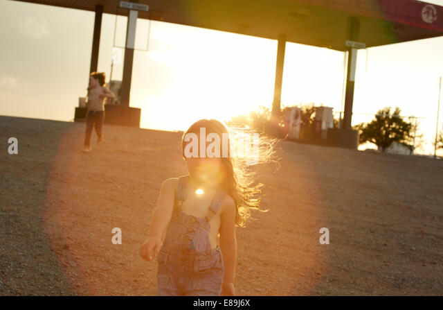 Kids at gas station at sunset - Stock Image