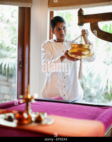 A spa therapist prepares the Sariva Room for a Shirodhara Ayurvedic Treatment at Ananda Spa, Ananda in the Himalayas. - Stock-Bilder