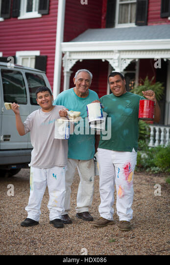 Smiling Hispanic men and boy posing with paint cans and paintbrushes - Stock Image