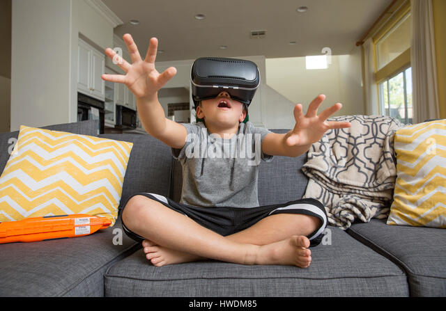 Young boy sitting cross legged on sofa, wearing virtual reality headset, hands reaching out in front of him - Stock-Bilder