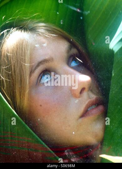 Vertical Young woman's face looking upwards wrapped in a green banana leaf matching her eyes. - Stock Image