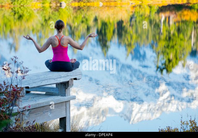 Woman meditating by lake, Bellingham, Washington, USA - Stock Image