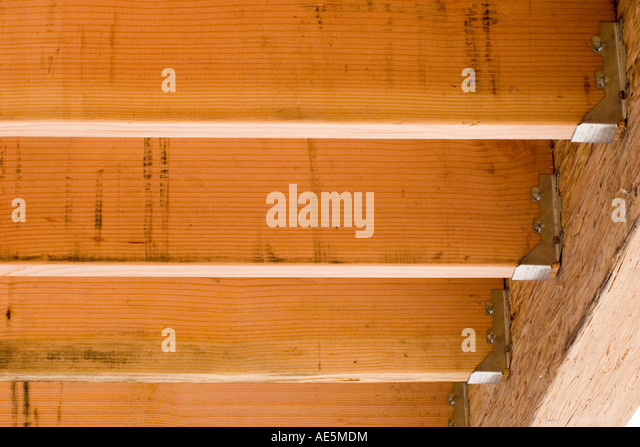 Floor joists attached to beam with joist hangers at a residential remodel construction site - Stock Image