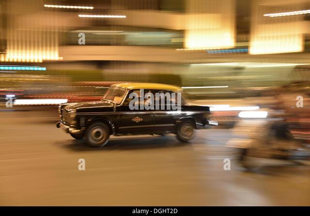 Taxi in motion on a street at night, Mumbai, Maharashtra, India - Stock Image