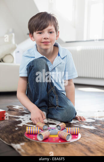 Portrait of boy playing with board game, smiling - Stock Image
