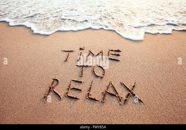 time to relax, concept written on sandy beach - Stock-Bilder
