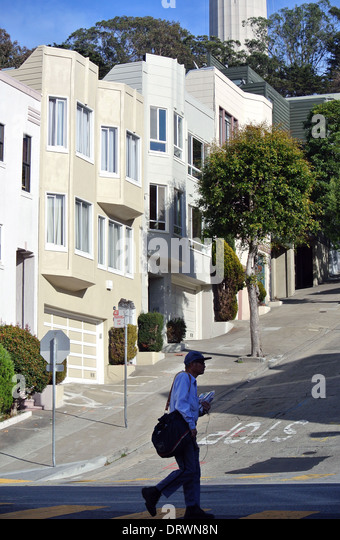 postman delivering mail on steep hill in San Francisco - Stock Image
