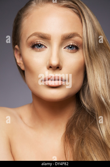 Close up portrait of pretty blond woman on gray background. Perfect face and makeup. Looking at camera. - Stock Image