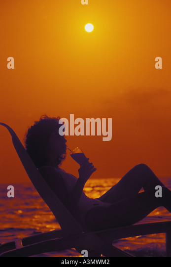 Beach Woman relaxing tropical drink orange background silhouette silo summer vacations - Stock Image