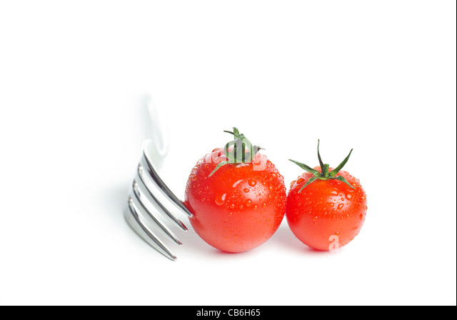 Fresh juicy cherry tomatoes with  a fork on a white background - Stock Image