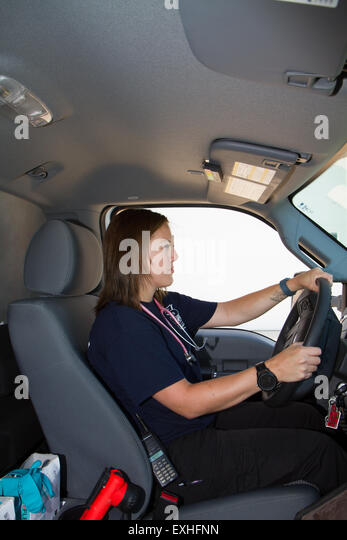 Female paramedic EMT using radio in ambulance. Rural volunteer fire department ambulance. - Stock Image