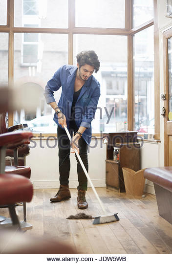 Man sweeping barbershop floor with broom - Stock-Bilder