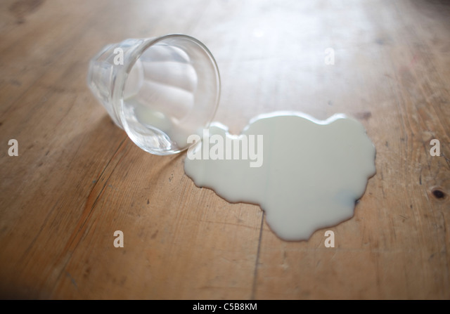 Glass of milk spilt on wooden floor - Stock Image