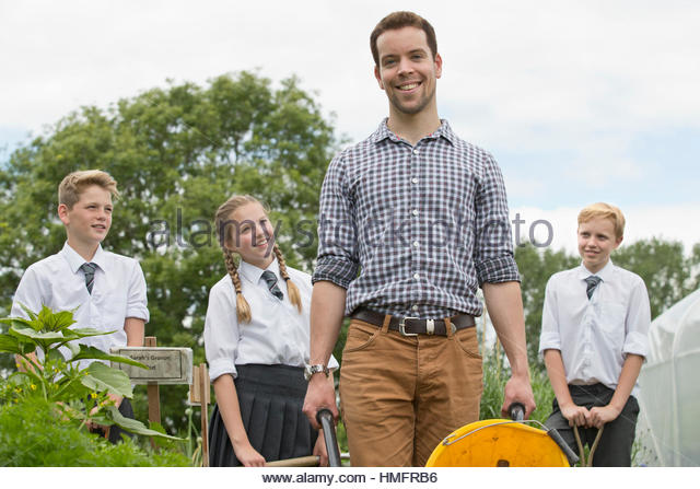 Portrait smiling teacher and middle school students learning gardening in vegetable garden - Stock-Bilder