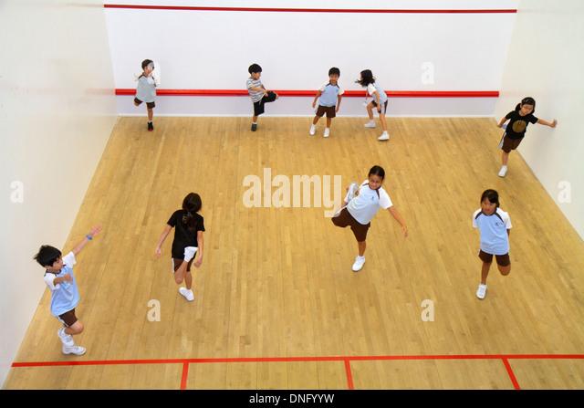 Hong Kong China Island Central Hong Kong Squash Centre center court class Asian boy girl student warm up warming - Stock Image