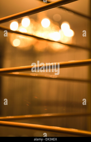 Abstract grill work with illuminated chandelier in background, close up - Stock-Bilder