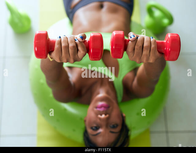 Young adult african american woman in sports clothing at home, doing domestic fitness and training pectorals on - Stock-Bilder