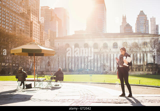 Woman waiting at Bryant Park against New York Public Library on sunny day - Stock-Bilder