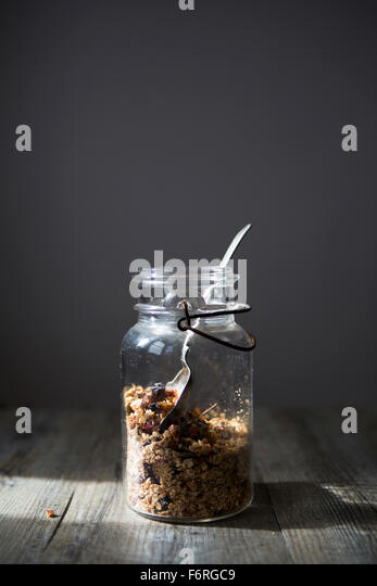 Jar of Homemade Granola with Nuts, Seeds Raisins & Cranberries with Spoon - Stock Image