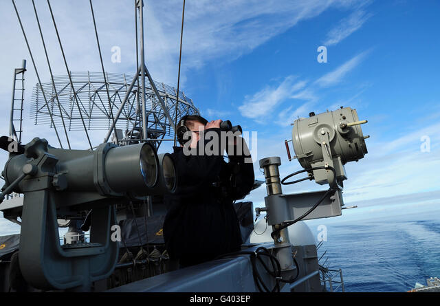 Seaman stands a port lookout watch aboard aircraft carrier USS Theodore Roosevelt. - Stock Image