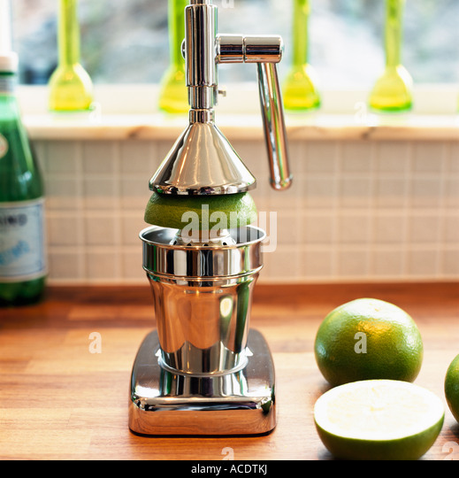 A juice press and lime fruits close-up. - Stock Image