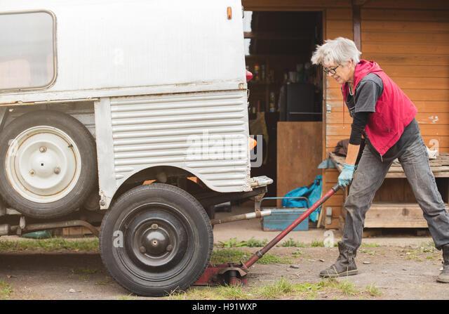 Elderly car mechanic jacking up vintage car - Stock-Bilder