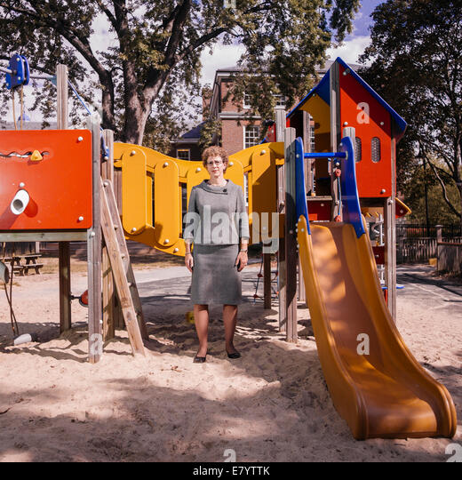 Middle-aged woman standing by slide at playground - Stock Image