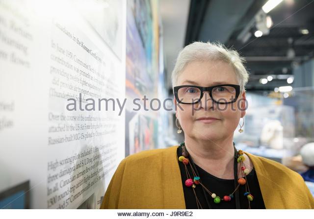 Portrait confident female senior docent at exhibit in war museum - Stock-Bilder