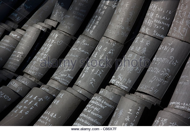 Religious roof tiles stacked on ground - Stock Image