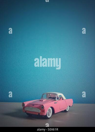 Classical pink vintage toy car on blue background - Stock Image
