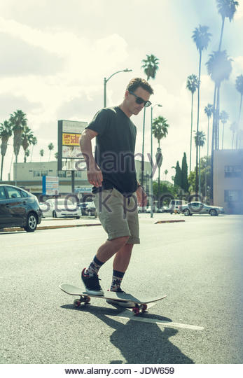 Young man on skateboard in street - Stock-Bilder