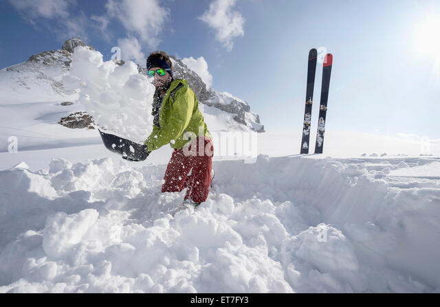 Man shovelling snow for bivouac camp, Tyrol, Austria - Stock Image