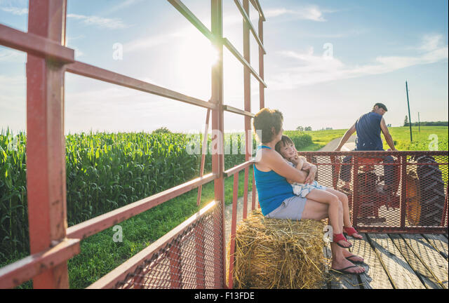 Mother sitting with her daughter in the back of a tractor - Stock Image