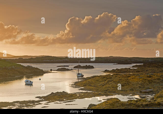 Tranquil sunset view fishing boats on lake, Harris, Outer Hebrides - Stock Image