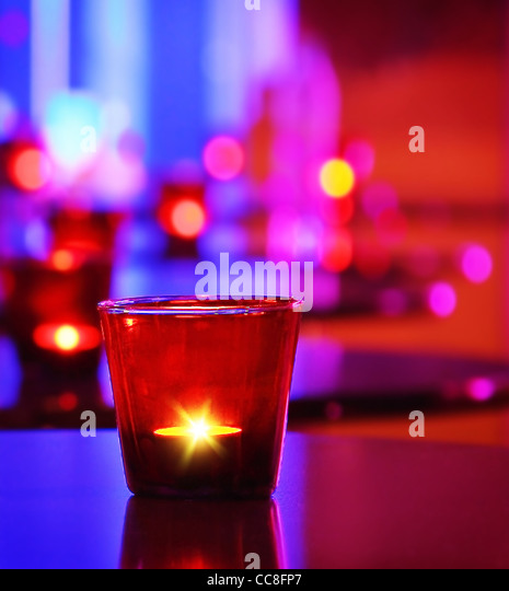 Romantic interior of a luxury restaurant with warm cozy candlelight - Stock Image