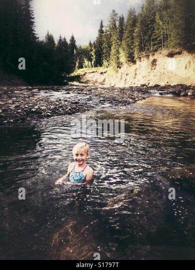 A girl wades in a wilderness creek. - Stock Image